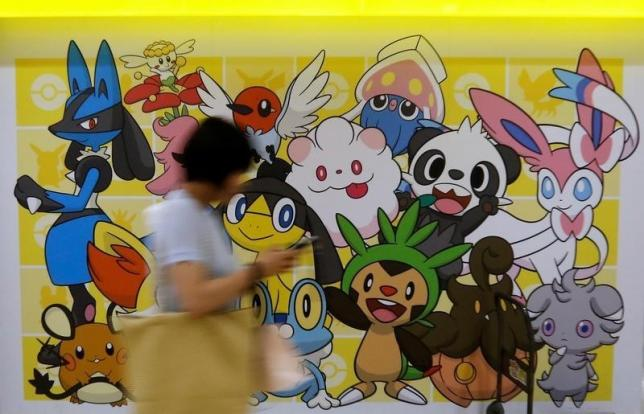 A woman using a mobile phone walks past a shop selling Pokemon goods in Tokyo